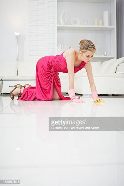 Woman scrubbing floor in evening gown