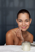 Woman scrubbing her face with sugar