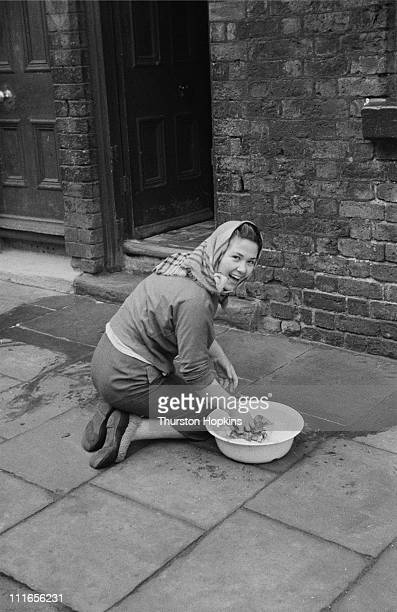 A woman scrubbing the front doorstep of her house in a slum area of Liverpool 19th November 1956 Original publication Picture Post 8995 Liverpool...