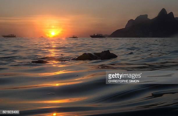 A woman sea bathes during sunset at Ipanema beach in Rio de Janeiro Brazil on December 18 2015 AFP PHOTO / Christophe SIMON / AFP / CHRISTOPHE SIMON
