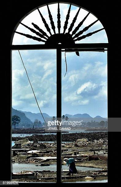 A woman searches among the ruins of her house in Ule Lhee outskirts of Banda Aceh 16 January 2005 three weeks since a devastated earthquake and...