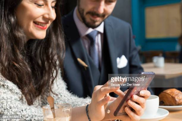 Woman searches internet on mobile phone, while partner looks on, sitting in cafe.