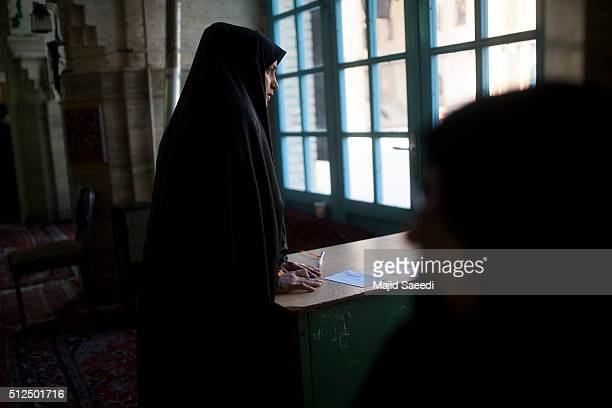 A woman searches the list of candidates during the parliamentary and Experts Assembly elections at a polling station on February 26 2016 in Qom 125...