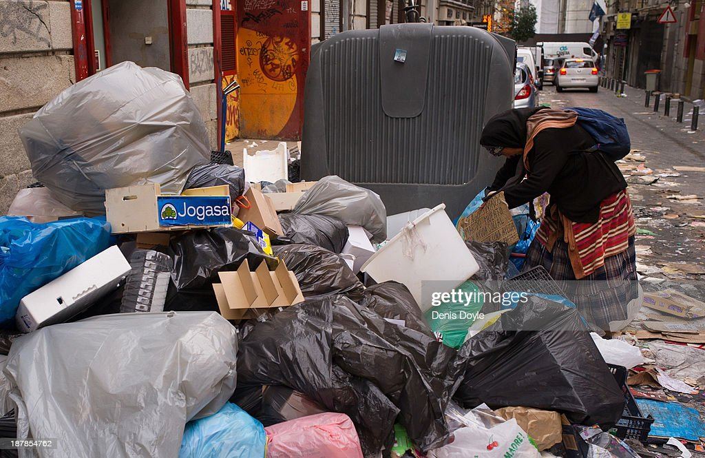 A woman searches through garbage in the city centre on November 13, 2013 in Madrid, Spain. Street cleaners, garbage collectors and public park gardeners working for Madrid city council started an indefinite strike 9 days ago after the private contracters plan to axe more than 1,000 jobs and introduce a 40% pay cut for the remaining workers.