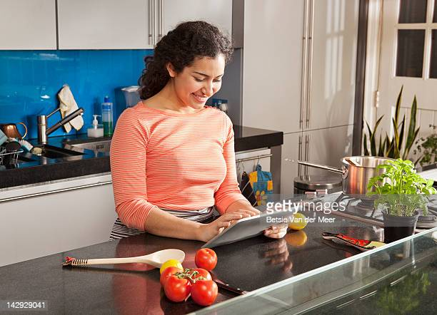 Woman searching ipad for recipes in kitchen.
