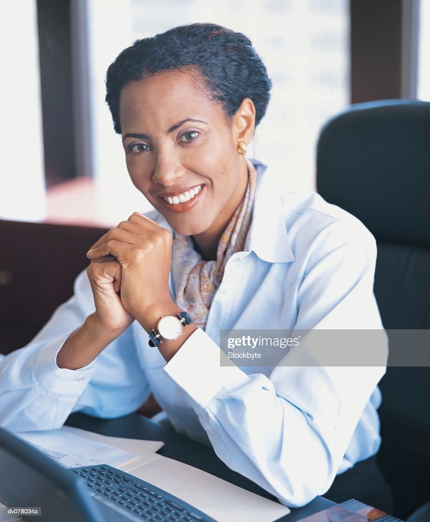 Woman seated at desk, smiling : Stock Photo