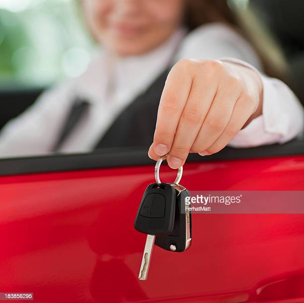Woman seated in a car holding keys out the window