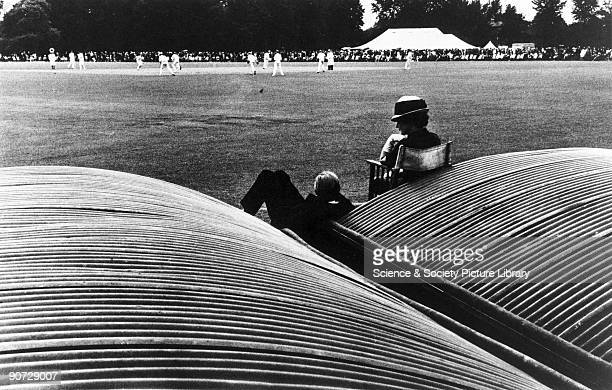 Woman seated in chair beside man reclining against the pitch covers watching a cricket match at the 'Fourth of June' event at Eton School in...