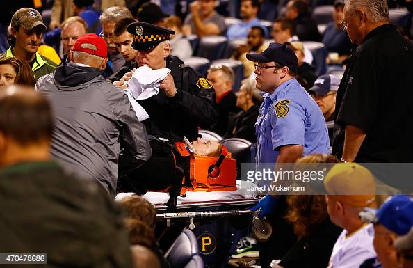 A woman seated in the Lexus Club section of PNC Park is taken out by EMT's and Pittsburgh Police on a stretcher after taking a foul ball to the back...