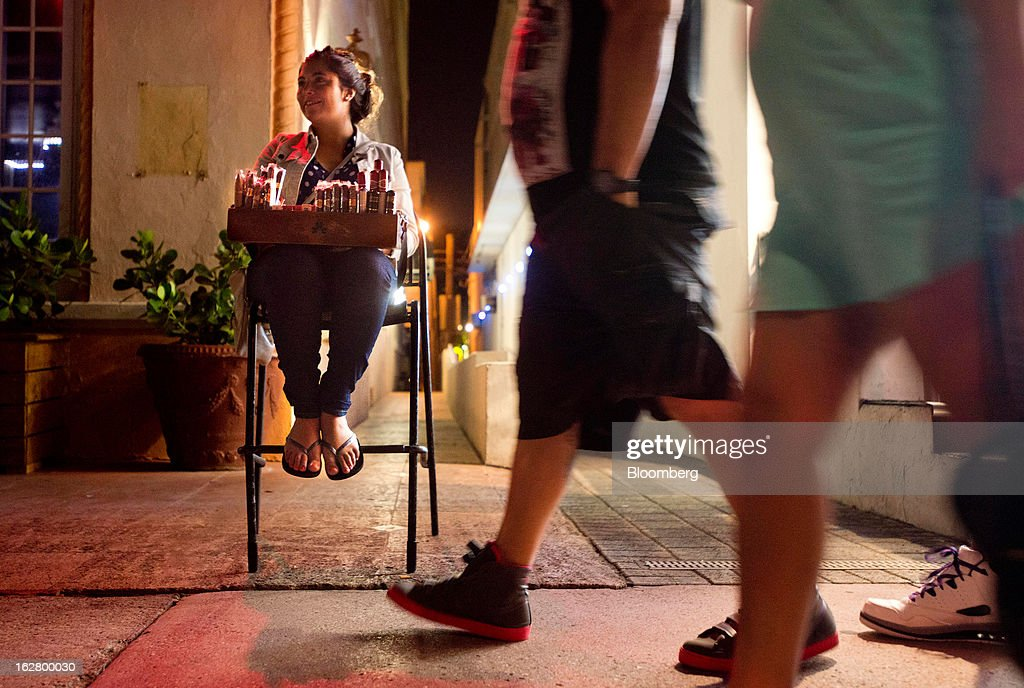 A woman seated on a chair on the sidewalk holds a box of cigars and cigarettes for sale as pedestrians walk by on Ocean Drive in the South Beach neighborhood of Miami Beach, Florida, U.S., on Tuesday, Feb. 19, 2013. U.S. exports in the travel and tourism sector reached $168.1 billion in 2012, up 10.1 percent from the year-ago level of $152.7 billion, according to data released Feb. 22 by the Commerce Department's International Trade Administration. Photographer: Ty Wright/Bloomberg via Getty Images