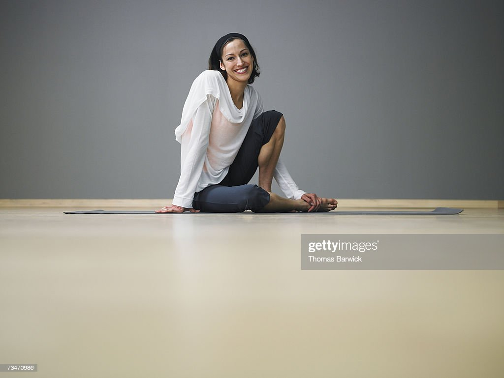 Woman seated on yoga mat in exercise studio, smiling : Stock Photo
