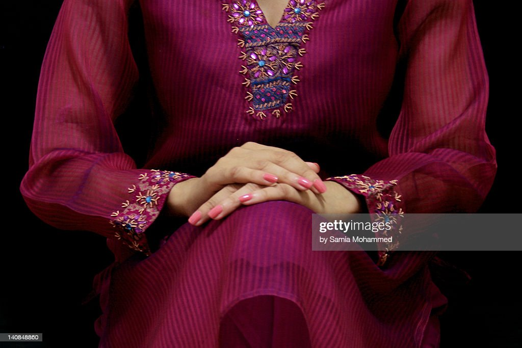 Woman seated with hands on lap : Stock Photo
