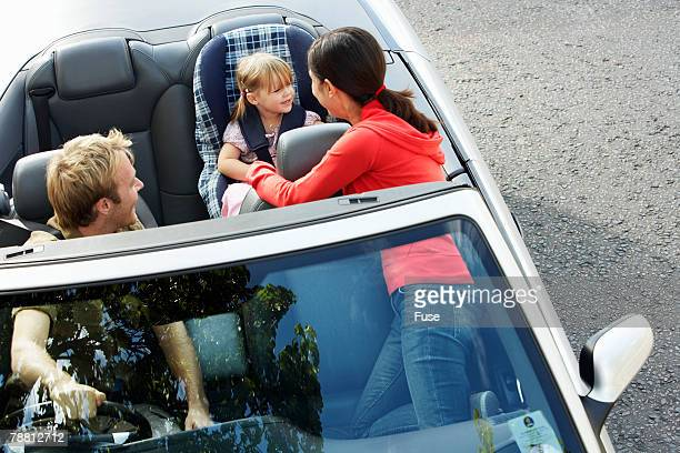 Woman Securing Child in a Car Seat