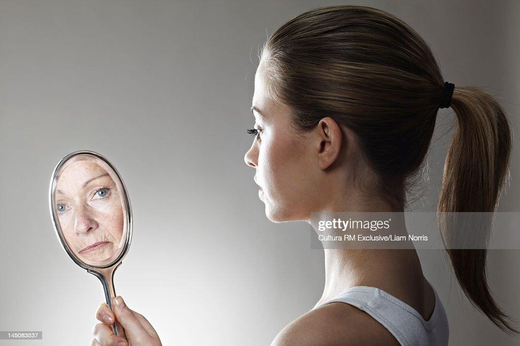 Woman seeing herself older in mirror