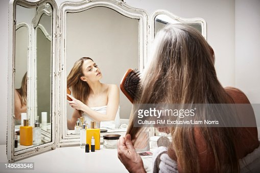 Woman seeing herself younger in mirror : Stock Photo