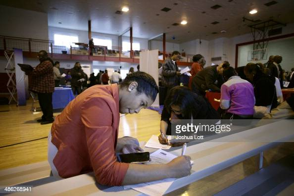 A woman seeking employment fills out an application at a job fair at the Matrix Center April 23 2014 in Detroit Michigan Several local organizations...