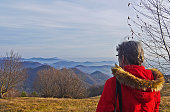 Woman seen from behind admiring winter view of rolling hills