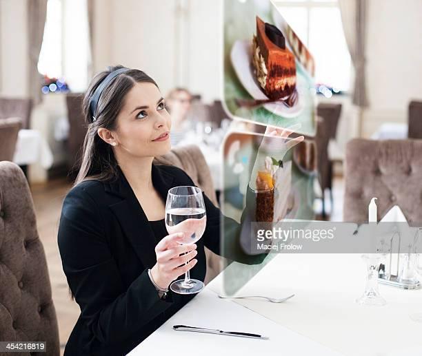 Woman selecting a dessert using interactive screen