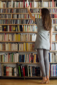 Woman selecting book from shelf, rear view
