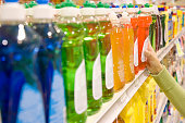 Woman selecting dishwashing liquid product in supermarket