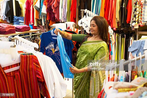 Woman selecting dress in supermarket