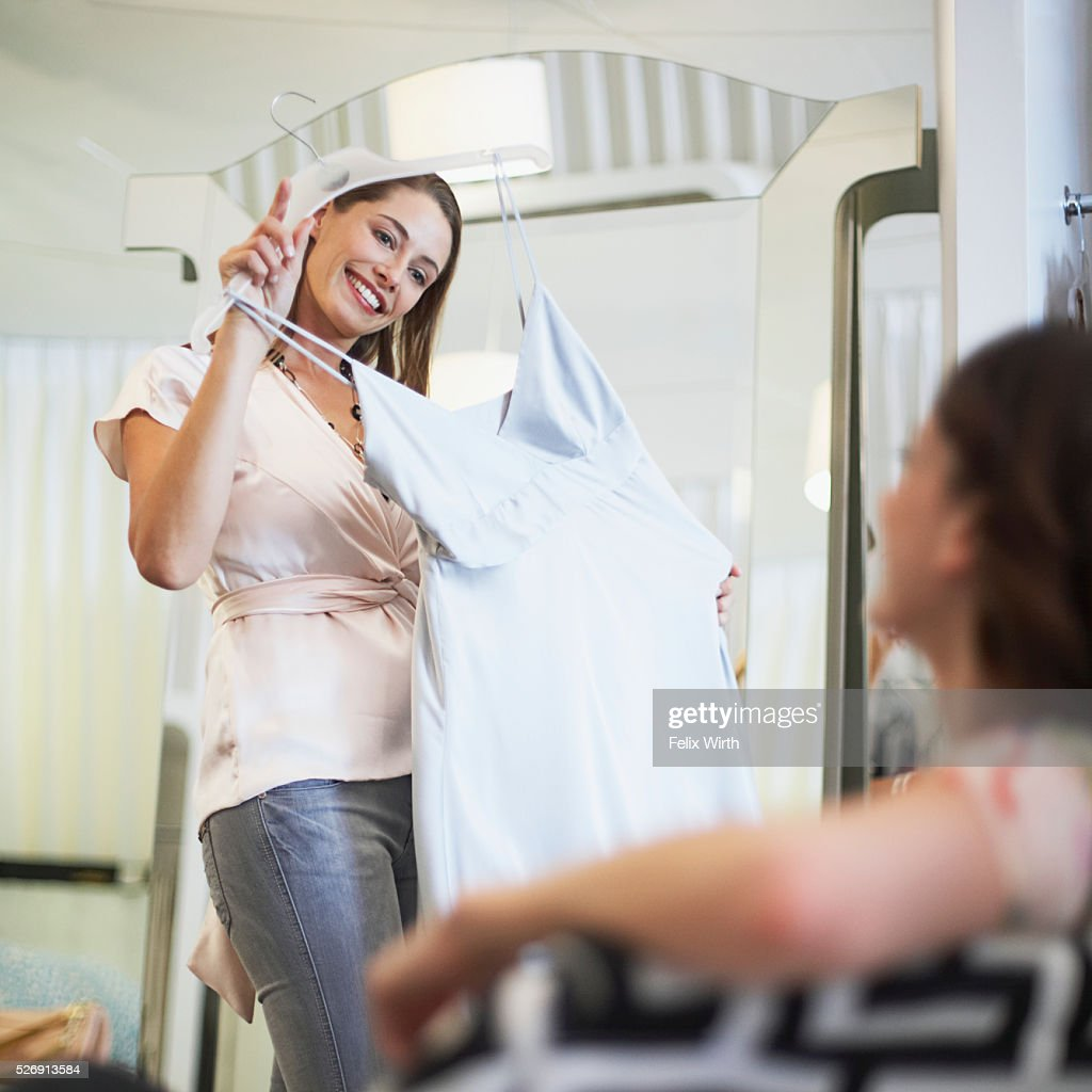 Woman selecting dress : Bildbanksbilder