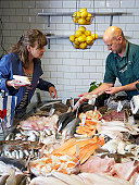 woman selecting fish from shop owner