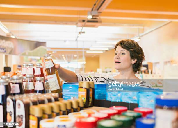 woman selecting food from shelf in supermarket