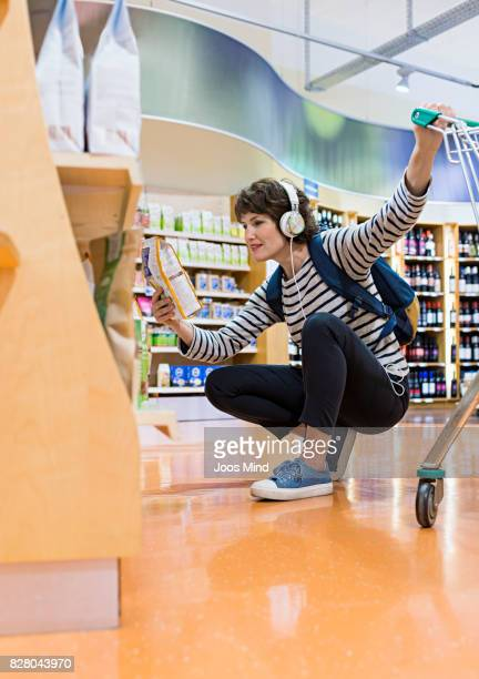 woman selecting groceries from shelf in supermarket