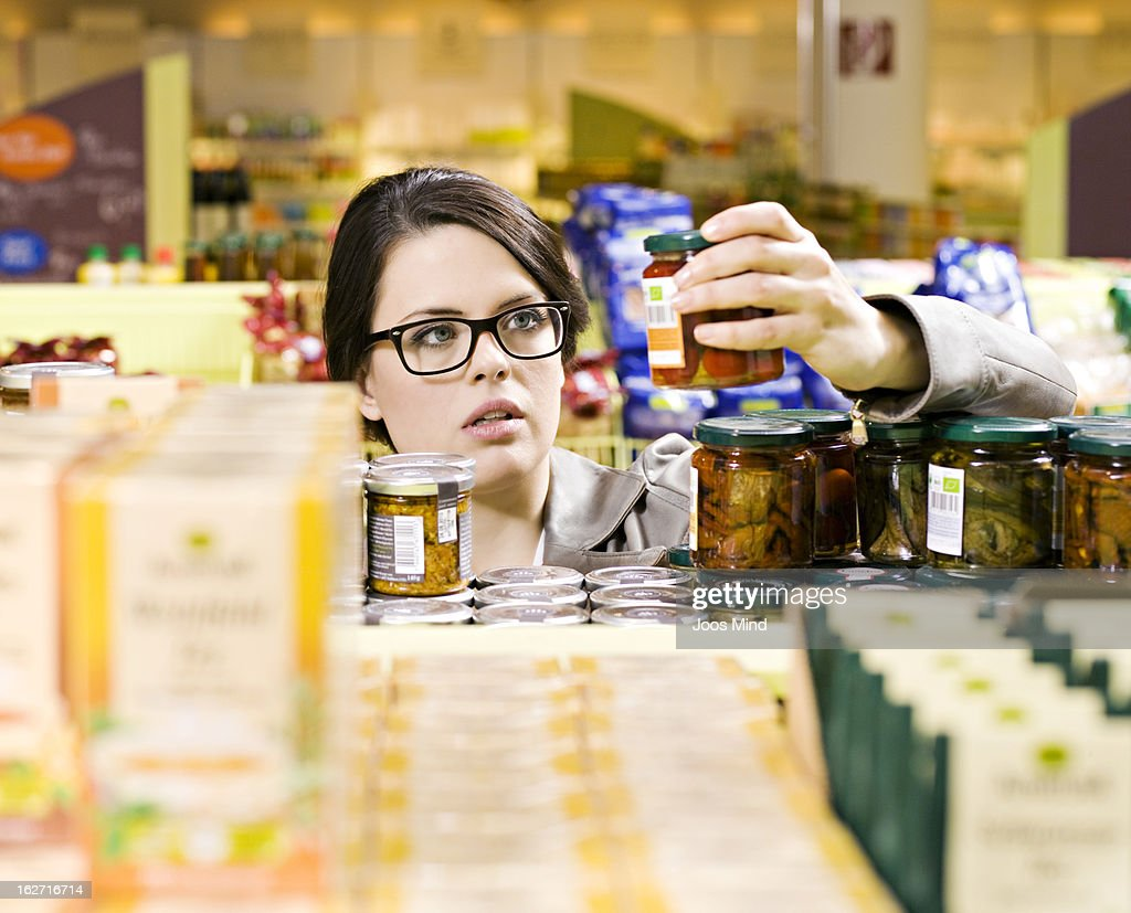 woman selecting jar from shelf in supermarket : Stock Photo