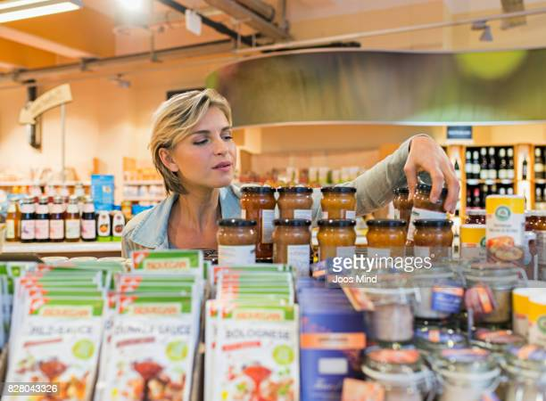woman selecting jar from shelf in supermarket