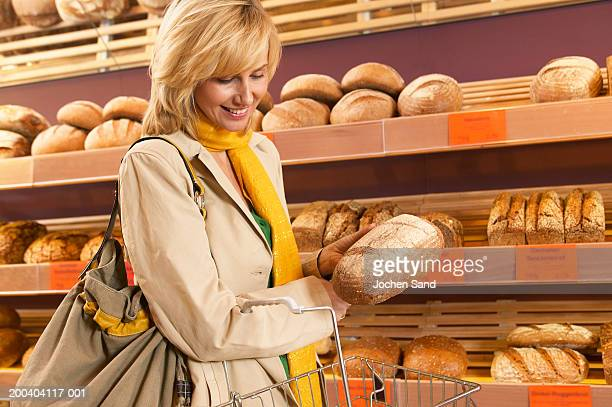 Woman selecting loaf of bread from shelf in supermarket, smiling