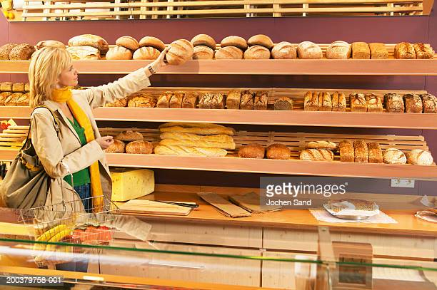 Woman selecting loaf of bread in supermarket