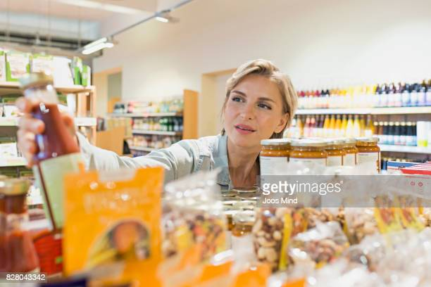 woman selecting product from shelf in supermarket