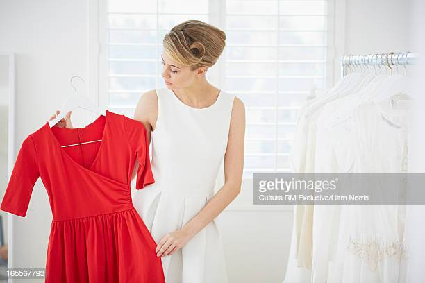 Woman selecting red dress in bedroom