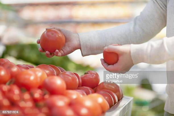 Woman selecting tomatoes at grocery store