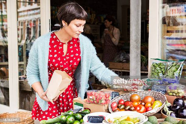 Woman selecting tomatoes at local farm shop.