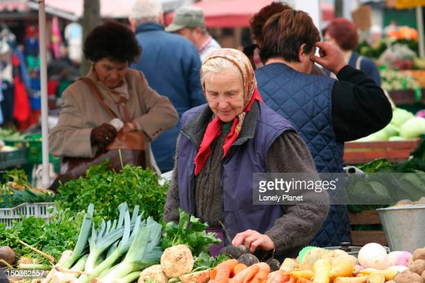 Woman selecting vegetables at open-air market near the Cathedral.