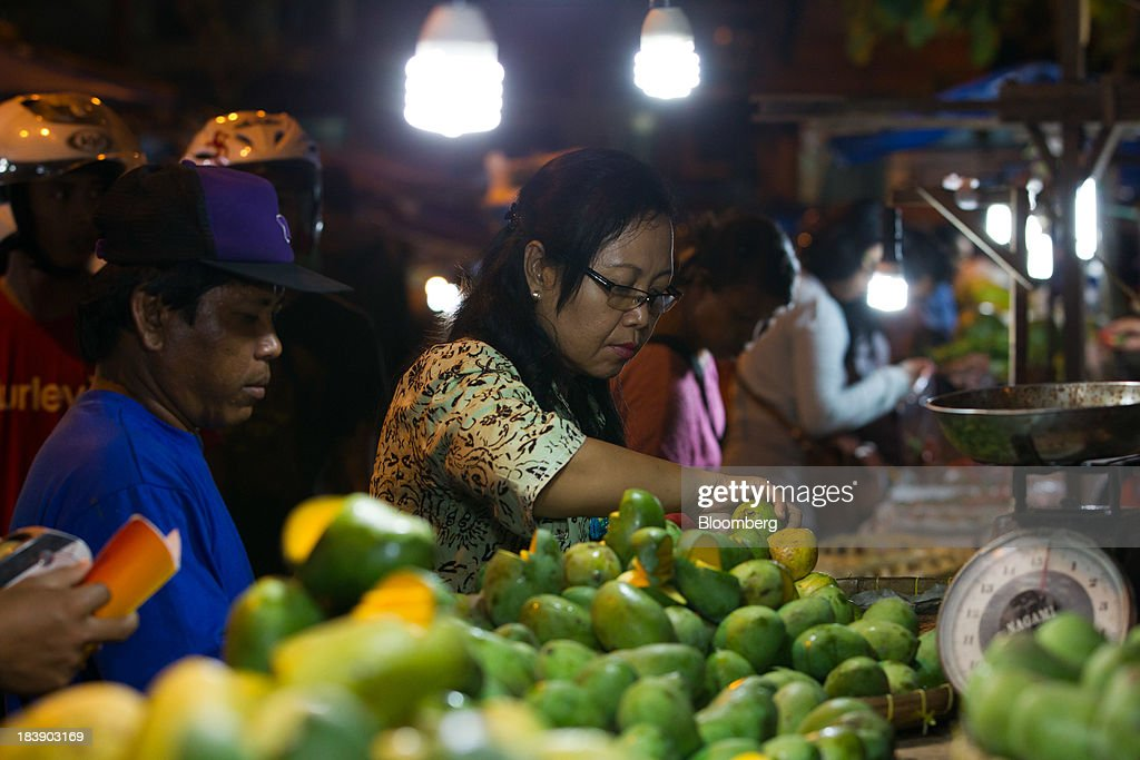 A woman selects mangos at the Pasar Badung market in Denpasar, Bali, Indonesia, on Tuesday, Oct. 8, 2013. Bank Indonesia said it will regulate currency hedging by individuals and companies, including state-owned firms, to help stabilize Asias most-volatile currency. Photographer: SeongJoon Cho/Bloomberg via Getty Images