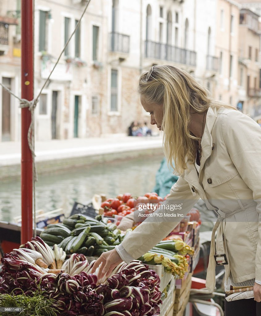 Woman selects produce from floating market, Venice : Stock Photo