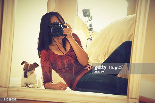 Woman self portrait in front of mirror with dog