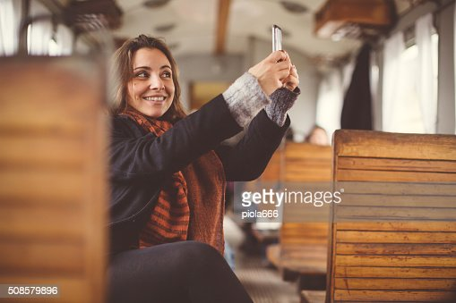 Woman selfie while travelling alone in a train : Stock Photo