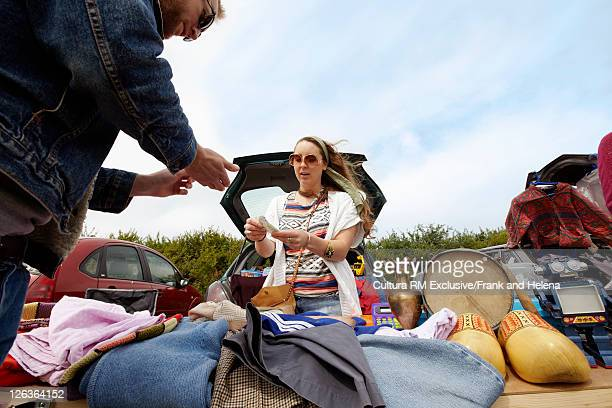 Woman selling clothes from car trunk