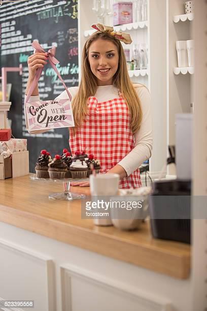 Donna vendita di cupcakes, con open-segnale inglese