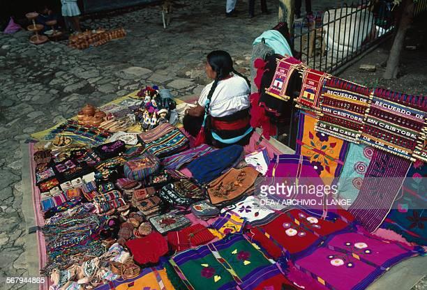 A woman selling fabric and bags in San Cristobal de Las Casas market Chiapas Mexico