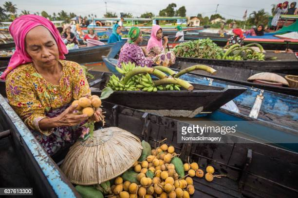 Woman selling fruit from a boat on a river in Borneo