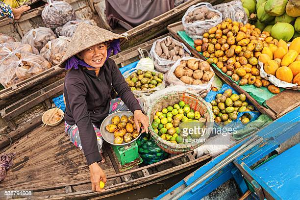 Woman selling fruits on floating market, Mekong River Delta,