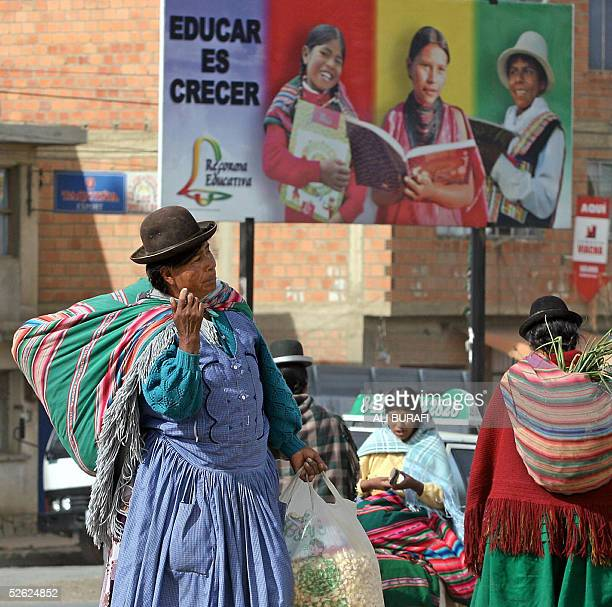 A woman selling 'pasan calla' walks in front of an add referring to an educational reform at El Alto 12 km from La Paz 11 March 2005 With a...