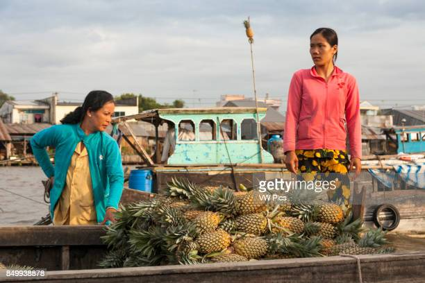 Woman selling pineapples from a boat in the floating market Cai Rang near Can Tho Mekong River Delta Vietnam