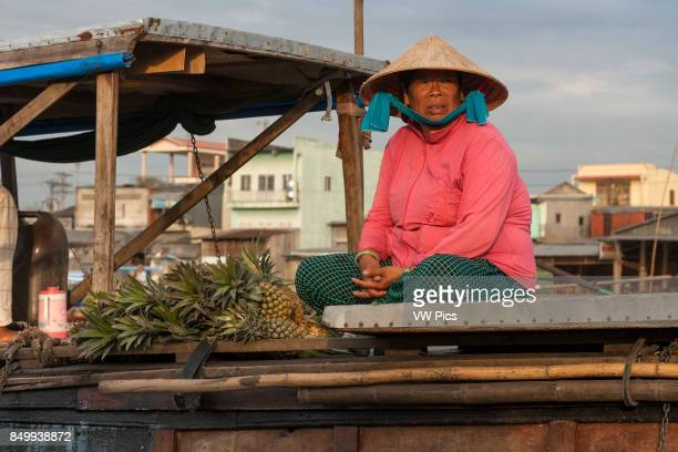 Woman selling pineapples in the floating market Cai Rang near Can Tho Mekong River Delta Vietnam
